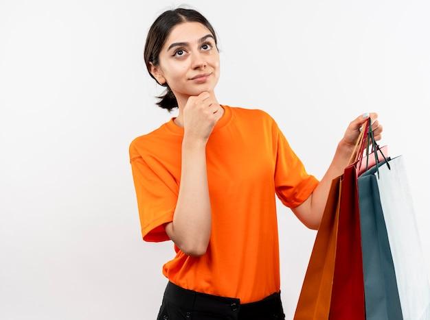 Ragazza che indossa la maglietta arancione che tiene i sacchetti di carta che osserva da parte in piedi perplesso sopra il muro bianco