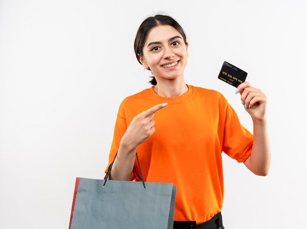 Young girl wearing orange t-shirt holding paper bags showing credit card pointing with finger at it smiling standing over white wall