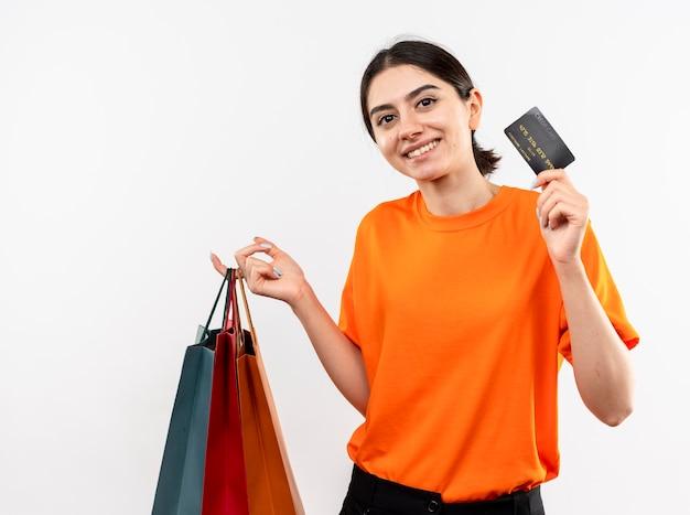 Ragazza che indossa la maglietta arancione che tiene i sacchetti di carta che mostrano la carta di credito che sorride con la faccia felice che sta sopra la parete bianca