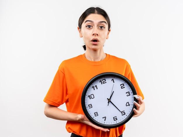 Giovane ragazza che indossa la maglietta arancione che tiene orologio da parete lookign alla telecamera essendo sorpreso e confuso in piedi su sfondo bianco