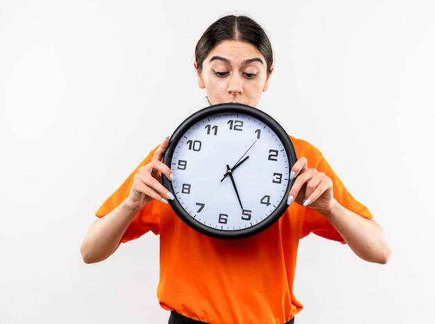 Giovane ragazza che indossa t-shirt arancione tenendo l'orologio da parete guardandolo con faccia seria in piedi sopra il muro bianco