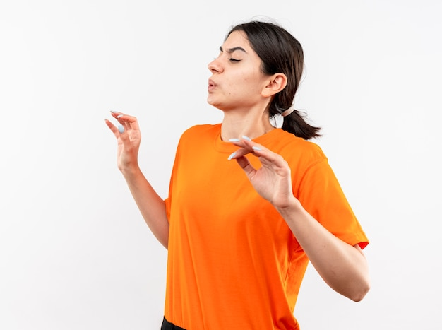 Young girl wearing orange t-shirt looking aside holding hands out with disgusted expression standing over white wall