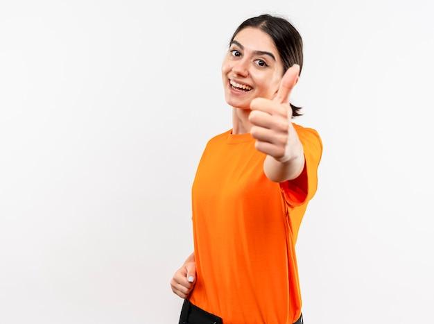 Молодая девушка в оранжевой футболке смотрит в камеру, весело улыбаясь, показывает палец вверх, стоя на белом фоне