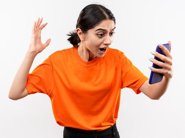 그녀의 스마트 폰 화면을보고 오렌지 티셔츠를 입고 어린 소녀 흥분하고 흰 벽 위에 서있는 제기 손으로 혼란