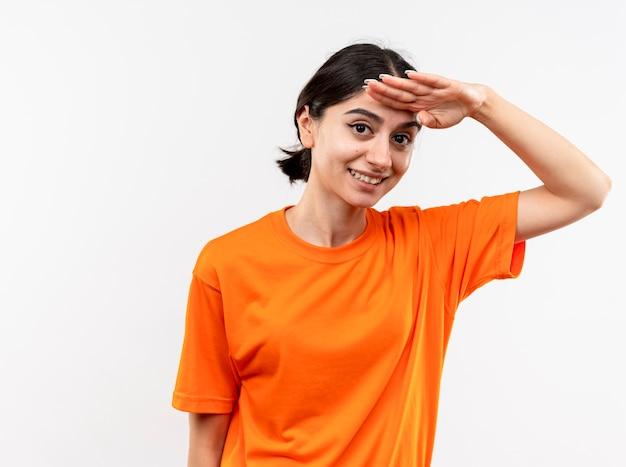 Giovane ragazza che indossa la maglietta arancione che guarda lontano con la mano sopra la testa sorridente in piedi sul muro bianco
