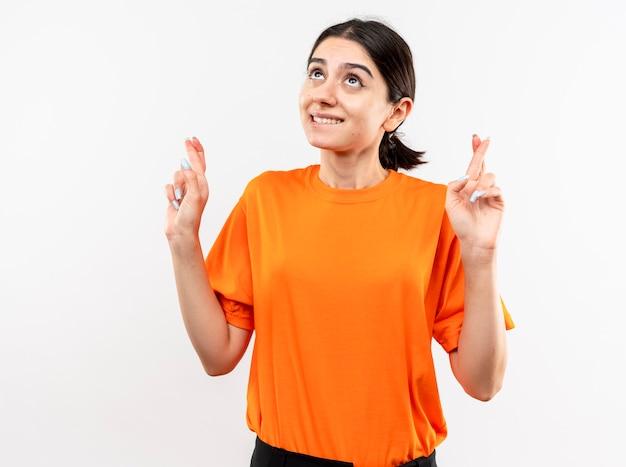 오렌지 티셔츠를 입고 어린 소녀 흰색 벽 위에 서있는 바람직한 소원 횡단 손가락을 만드는 입술을 물고 올려