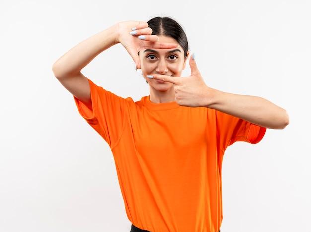 이 프레임을 통해 손가락으로 프레임을 만드는 주황색 티셔츠를 입고 어린 소녀는 흰 벽 위에 서서 웃고