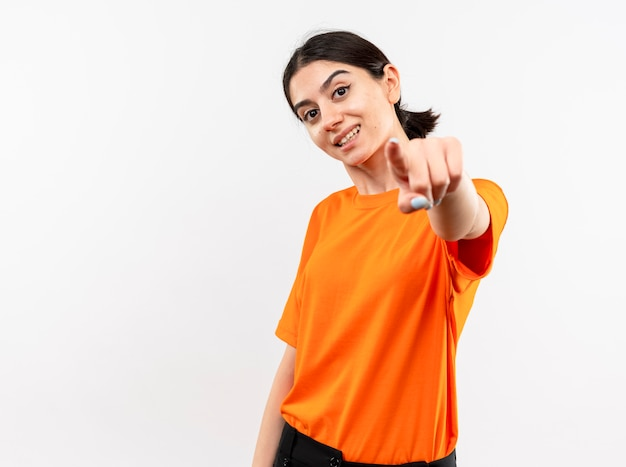 Young girl wearing orange t-shirt pointing with index finger at you smiling with happy face standing over white wall