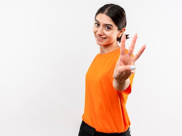 오렌지 티셔츠를 입고 어린 소녀가 흰 벽 위에 서있는 손가락 3 번으로 가리키고 웃고