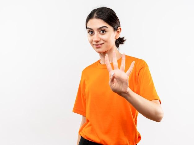 오렌지 티셔츠를 입고 어린 소녀가 흰 벽 위에 서있는 4 번을 손가락으로 가리키고 웃고