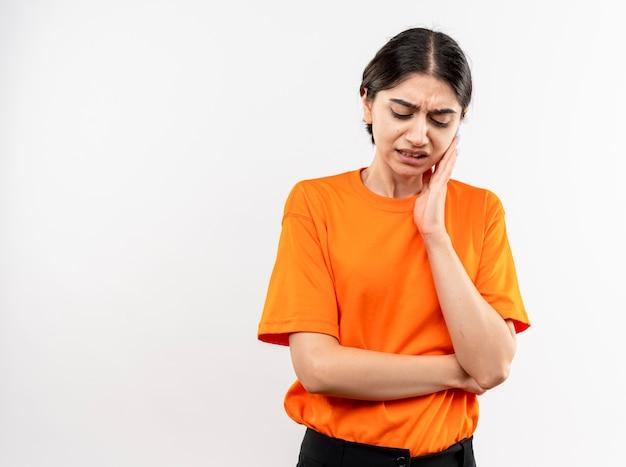Giovane ragazza che indossa la maglietta arancione toccando la sua guancia sensazione di mal di denti in piedi sopra il muro bianco