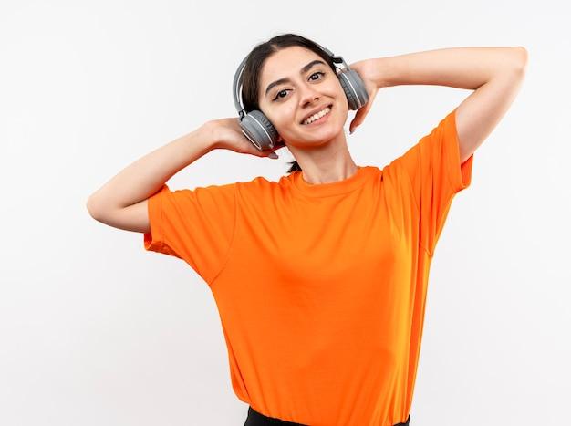 Молодая девушка в оранжевой футболке с наушниками счастлива и позитивна, наслаждаясь своей любимой музыкой, улыбаясь, стоя над белой стеной