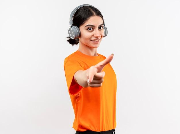 Giovane ragazza che indossa la maglietta arancione con le cuffie felice e positiva godendo la sua musica preferita sorridente puntando con il dito indice in piedi sul muro bianco