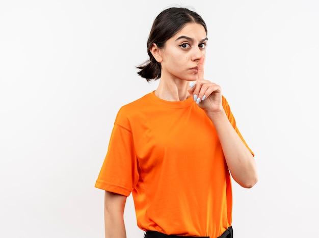 白い壁の上に立っている唇に指で沈黙のジェスチャーを作る深刻な顔のオレンジ色のtシャツを着ている若い女の子