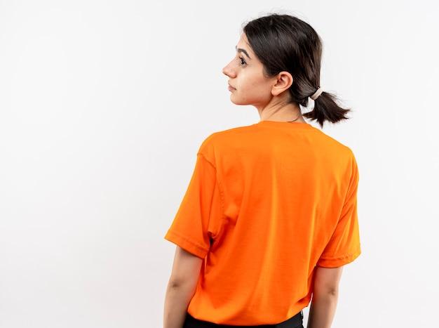 Молодая девушка в оранжевой футболке, глядя в сторону спиной на белой стене