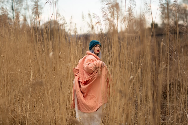 A young girl wearing a pastel coat and a stylish hat poses in a wheat field. back viev