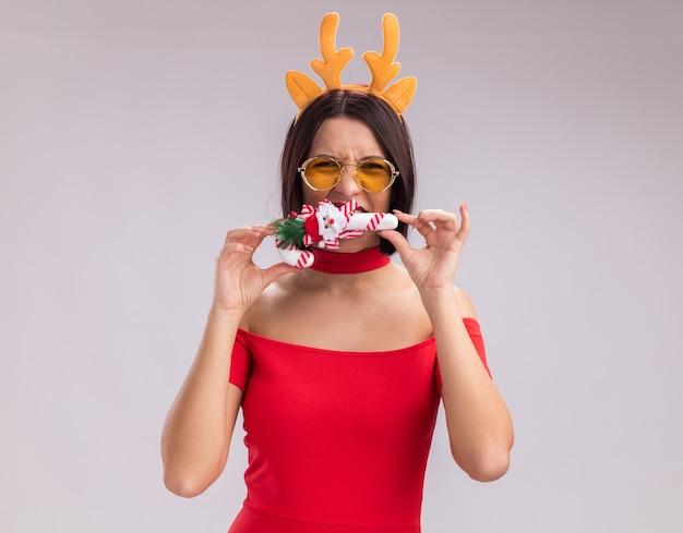 トナカイの角のヘッドバンドと白い背景で隔離のカメラを見てそれを噛んで口の近くにクリスマスキャンディケインの飾りを保持しているメガネを身に着けている若い女の子