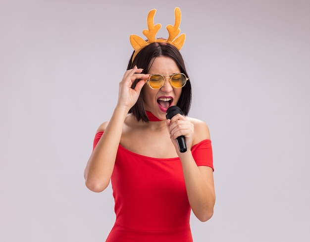 Young girl wearing reindeer antlers headband and glasses holding microphone grabbing glasses singing with closed eyes isolated on white background with copy space