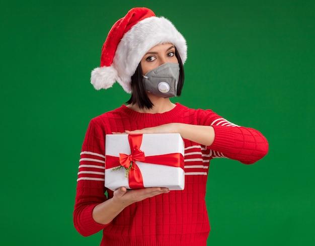 Молодая девушка в шляпе санта-клауса и защитной маске держит подарочную упаковку, изолированную на зеленой стене