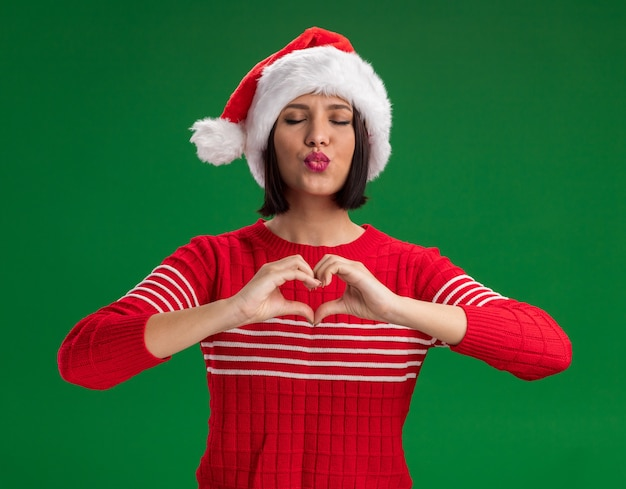 Young girl wearing santa hat doing heart sign and kiss gesture with closed eyes isolated on green wall