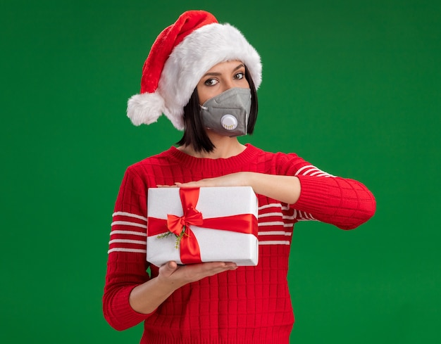 Young girl wearing santa hat and protective mask  holding gift package  isolated on green wall