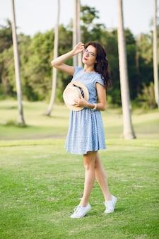 하늘색 드레스를 입고 어린 소녀는 열대 공원에 서 있습니다. 소녀는 손에 밀짚 모자와 검은 안경에 있습니다.