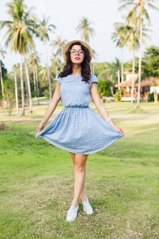 Young girl wearing sky-blue dress is standing on tip-toes in a park. girl has straw hat and black glasses on