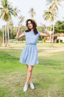 La ragazza che indossa un abito azzurro è in piedi in punta di piedi in un parco. la ragazza ha il cappello di paglia e gli occhiali neri