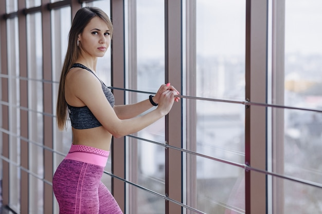 Young girl wearing sportswear in a gym near the window
