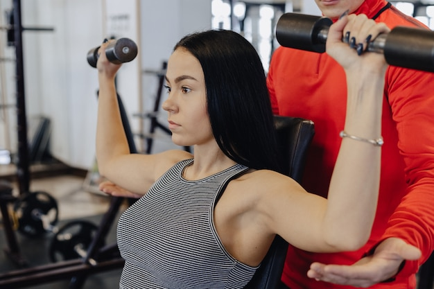 A young girl wearing sportswear in a gym performs dumbbell exercises