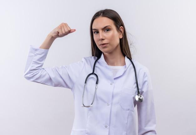 Молодая девушка в медицинском халате со стетоскопом делает сильный жест на изолированной белой стене