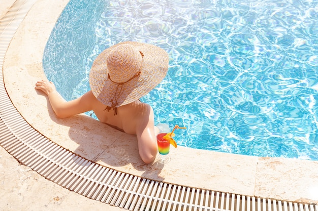 Young girl wearing sun hat siting by the pool with cocktail