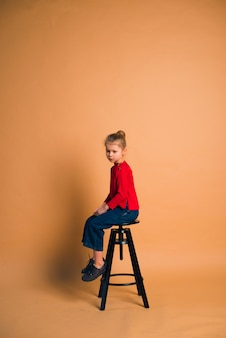 Young girl wearing trendy fashion outfit sitting on high stool in studio with color background
