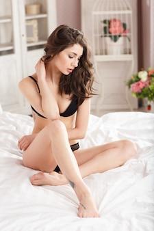ベッドの上に黒の下着を着ている若い女の子