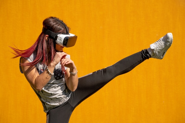Young girl wearing vr glasses and fighting in a yellow background