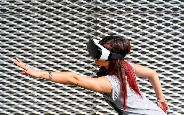 Young girl wearing vr glasses and headphones in a grey background