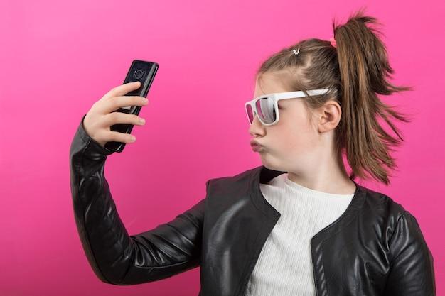 若い女の子は黒い革のジャケットを着て、彼女の携帯電話で写真を撮ります。ピンクで隔離