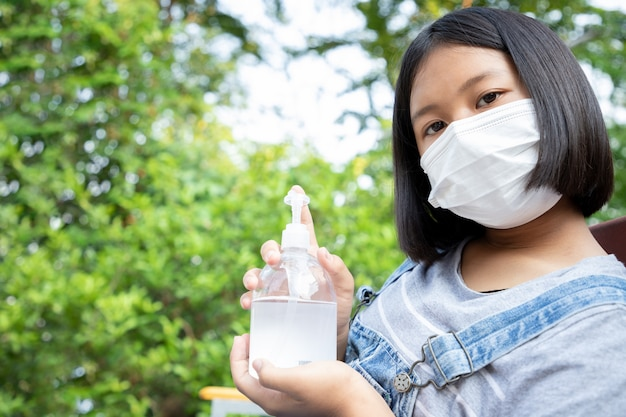 Young girl wears a protection mask and  have a headache and quarantine to monitor the infection from the virus in the garden at home. concept of social distance.
