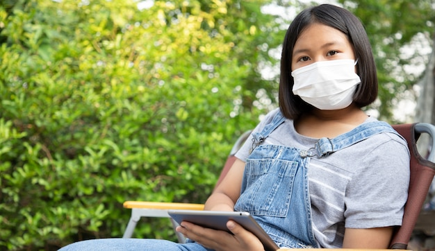 Young girl wears a protection mask and uses the tablet to study online in the garden at home. prevent contact from the coronavirus. concept of social distance. education from home.