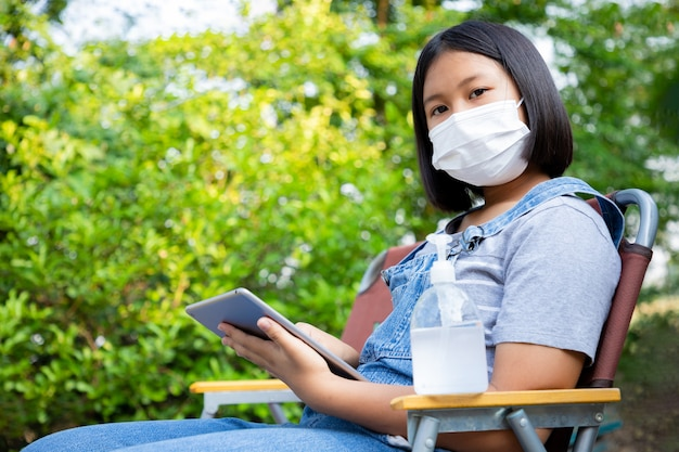 Young girl wears a protection mask with alcohol gel and uses the tablet to study online in the garden at home. prevent contact from the coronavirus.