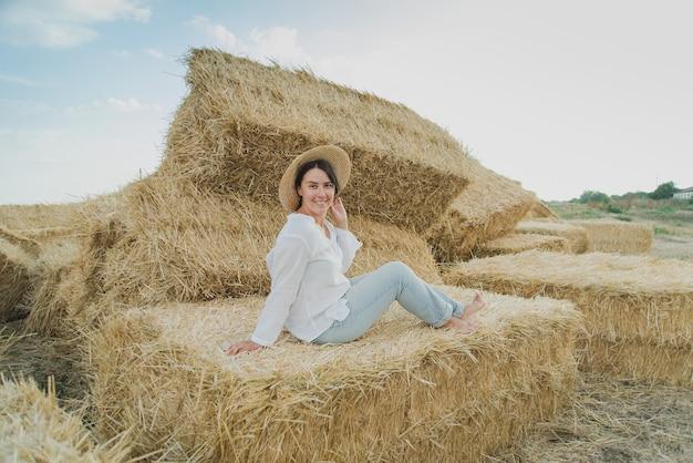 Young girl wears summer white dress near hay bale in field.