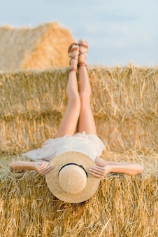 Young girl wears summer white dress near hay bale in field.
