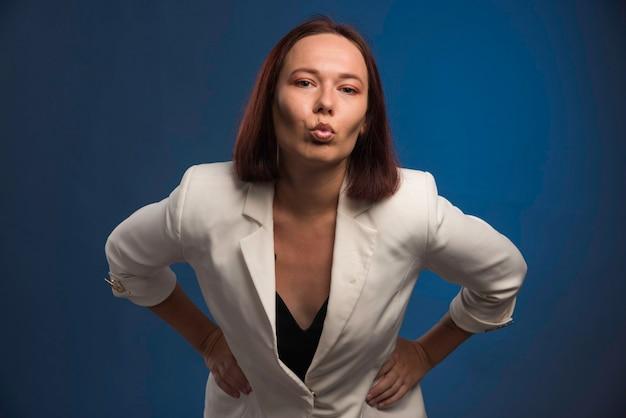 Young girl in white blazer sending kiss.
