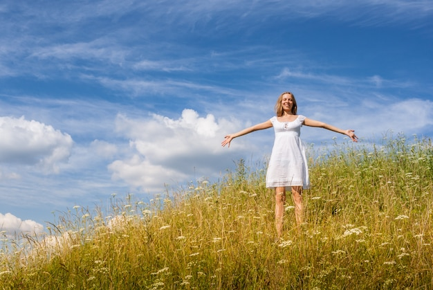 Young girl in white dress is standing on grass hill on blue sky background in summer day.