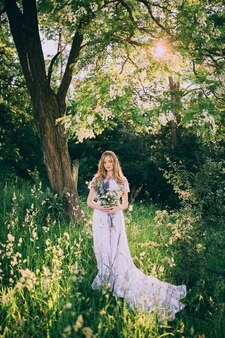 Young girl in a white dress in the meadow. woman in a beautiful long dress posing in the garden