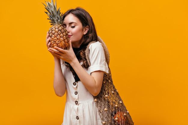Giovane ragazza in abito bianco con la borsa della spesa sulla sua spalla annusando ananas su sfondo arancione.