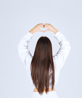 Young girl in white hoodie showing heart with two hands.