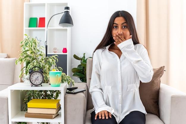 Giovane ragazza in camicia bianca e pantaloni neri, scioccata che copre la bocca con la mano seduta sulla sedia in un soggiorno luminoso light