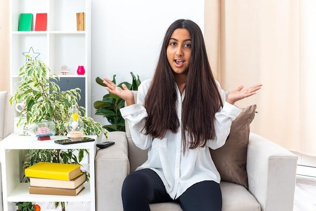 Giovane ragazza in camicia bianca e pantaloni neri che sembra confusa allargando le braccia ai lati seduta sulla sedia in un soggiorno luminoso Foto Gratuite