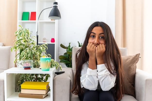 Giovane ragazza in camicia bianca e pantaloni neri stressata e nervosa che si morde le unghie seduta sulla sedia in un soggiorno luminoso